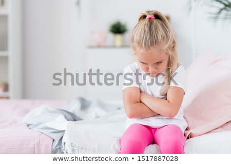 Offended or bored child crossing arms on chest while sitting on couch Stock photo © pressmaster