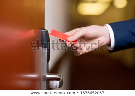 Hand of modern businessman holding red plastic card by closed wooden door Stock photo © pressmaster