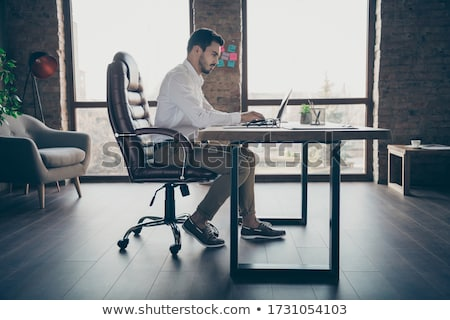 Worker Sitting at Desk on Chair Works at Computer Stock photo © robuart