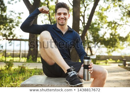 Image of young sportsman drinking water while doing workout on y Stock photo © deandrobot