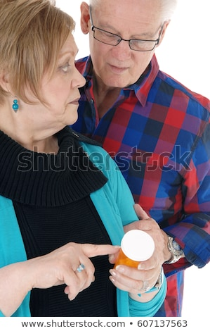 Stock photo: Elderly woman reading pill bottles