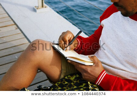 attractive young man with writing pad on the beach stock photo © victoria_andreas