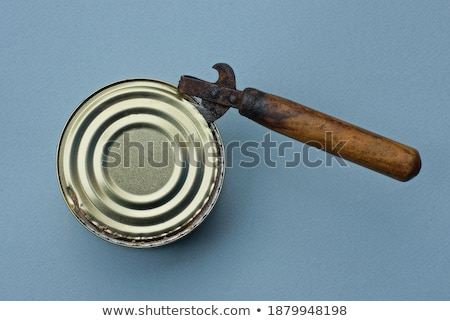 The old tin opener opening a can on wooden table Stock photo © inxti