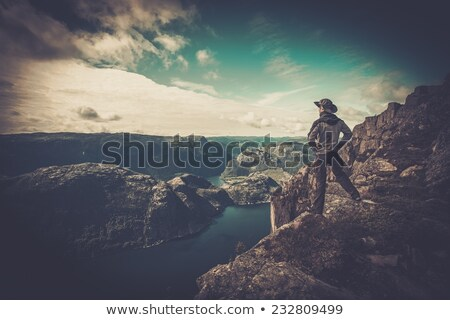 Man hiker looking over fjord panorama Stock photo © Nejron