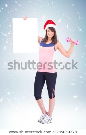 Festive brunette smiling at camera holding poster Stock photo © wavebreak_media