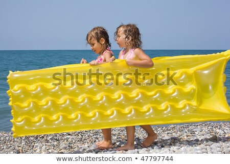 two pretty little girls bearing in hands inflatable mattress on  Stock photo © Paha_L