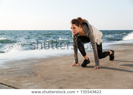photo of young brunette sport woman preparing to run seaside ou stock photo © deandrobot