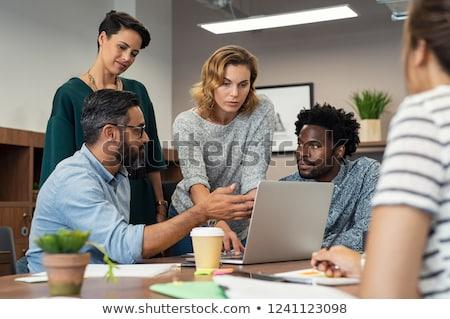cztery · osoby · lobby · wskazując · laptop · uśmiechnięty · zespołu - zdjęcia stock © is2
