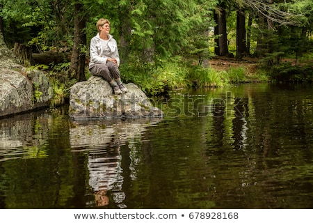 woman sitting on a rock in the woods stock photo © is2