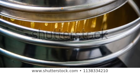 Strain the poured honey through a sieve. How to Harvest Honey. Filtering raw honey. Stock photo © FreeProd