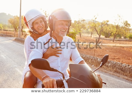 Middle age woman riding motor scooter Stock photo © dashapetrenko