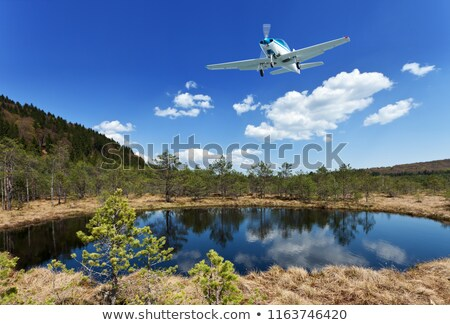 Exploring the wilderness - small aircraft flying above scenic vi Stock photo © lightkeeper