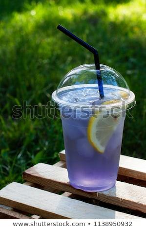 Stock photo: Lavender lemonade with lemon and ice on purple background.