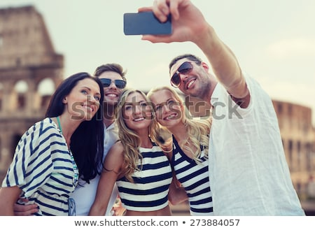 friends taking selfie by smartphone over coliseum stock photo © dolgachov
