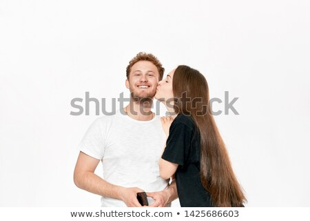 Portrait of lovely woman kissing caucasian man on cheek, while s Stock photo © deandrobot