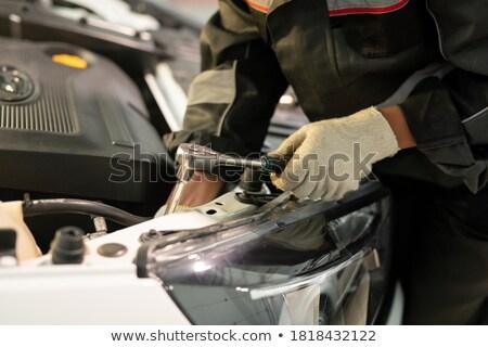 Gloved engineer of contemporary machine repair service with worktool Stock photo © pressmaster