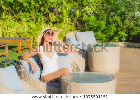 Stock photo: Young woman lounging around the pool