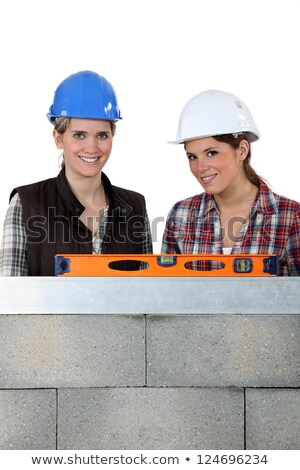 two craftswomen measuring a wall with a level Stock photo © photography33
