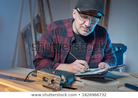 Man with a saw sitting on a workbench Stock photo © photography33