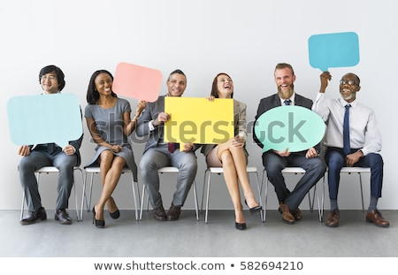 Businessman holding a blank speech bubble and thinking Stock photo © bmonteny