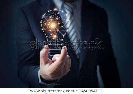 Stock photo: Hand holding a Bright Light Bulb
