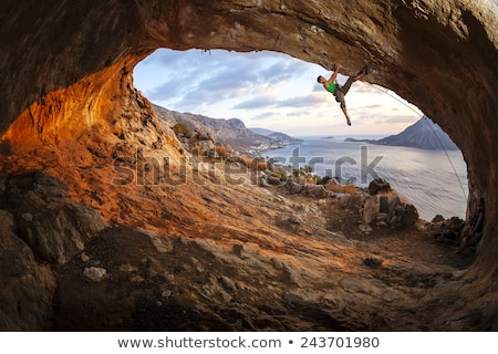 Mannelijke rock klimmen dak grot zonsondergang Stockfoto © photobac