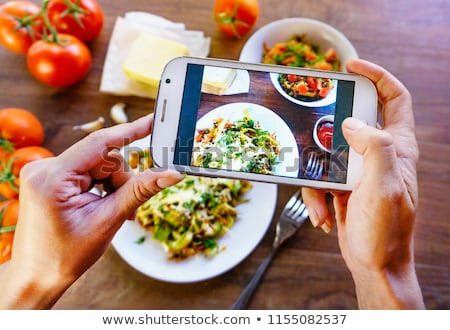 Woman making photo of food on smartphone Stock photo © deandrobot