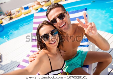 Girl friends tanning at swimming pool in front of water Stock photo © Kzenon