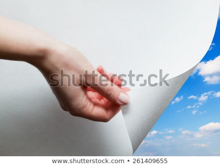 hand pulling edge of a paper to uncover reveal blue sky stock photo © photocreo