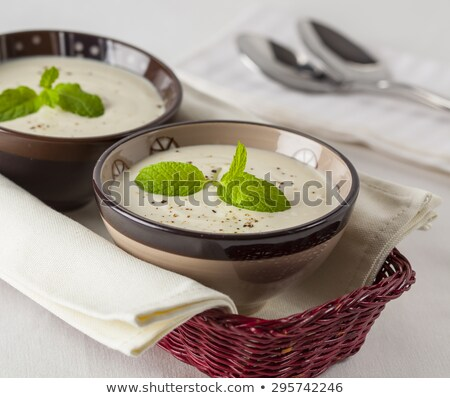 Green Cream of asparagus soup with shrimp in a white bowl on a r Stock photo © Yatsenko