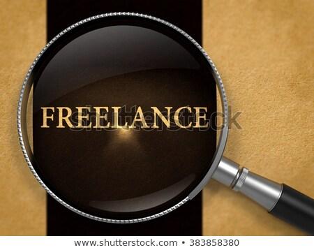 Freelance through Loupe on Old Paper. Stock photo © tashatuvango