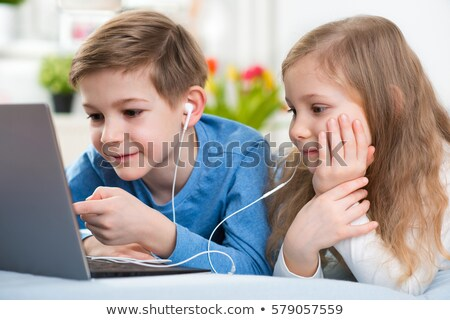happy little girl playing laptop and listening music stock photo © goce