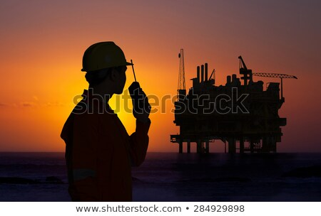 Worker using walkie talkie on oil rig Stock photo © IS2