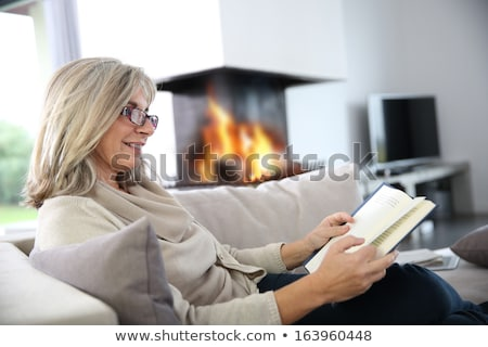 Senior woman reading book by fire Stock photo © IS2
