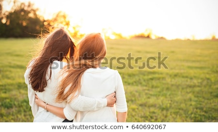 two cheerful young girls friends walking together stock photo © deandrobot