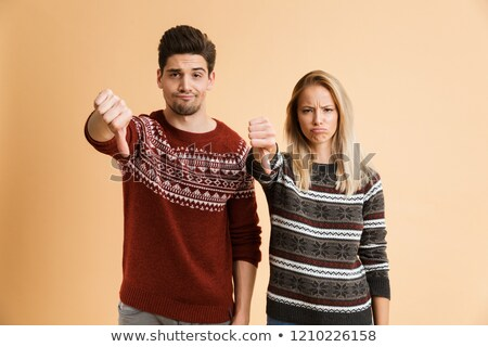 Portrait of an upset young couple dressed in sweaters Stock photo © deandrobot
