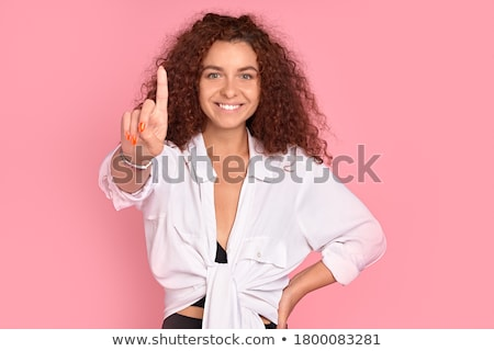 Pretty young woman posing isolated over pink wall background holding lipstick doing makeup. Stock photo © deandrobot