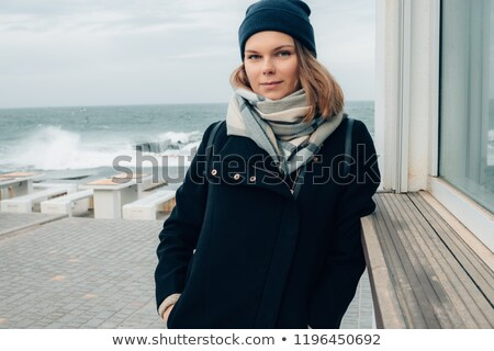 A young woman travels in comfortable clothes and stands near a white building Stock photo © ElenaBatkova