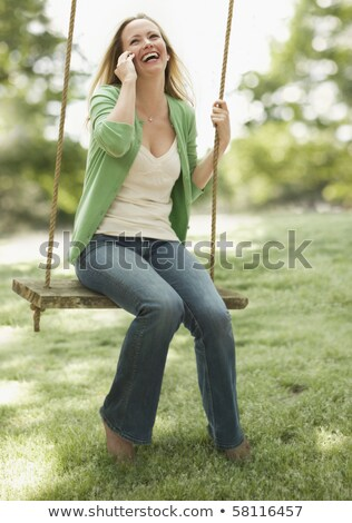 Woman seated on lawn talking on her mobile Stock photo © stryjek