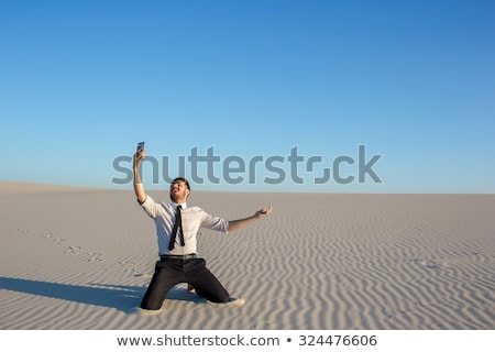 poor signal businessman searching for mobile phone signal in desert stock photo © master1305