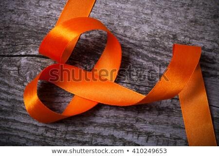 orange ribbon on a wooden surface stock photo © nito