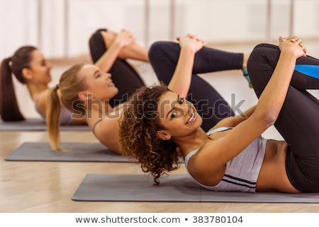 Concentrated sports woman doing abs exercise while lying on bench Stock photo © deandrobot