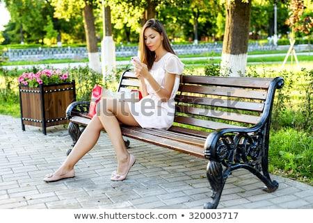 cheerful young girl sitting on a bench at the park stock photo © deandrobot