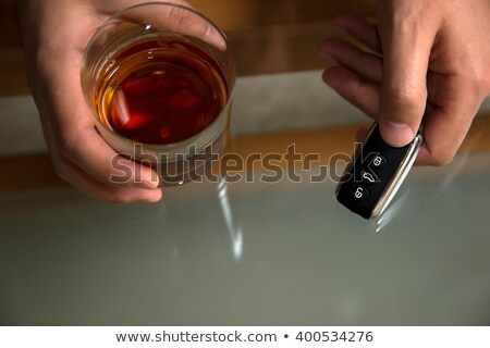 close up of hand with alcohol and car key on table Stock photo © dolgachov