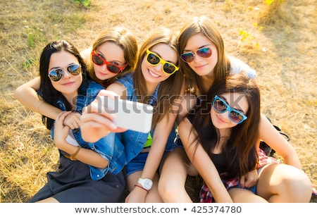 friends taking selfie by smartphone and hugging stock photo © dolgachov
