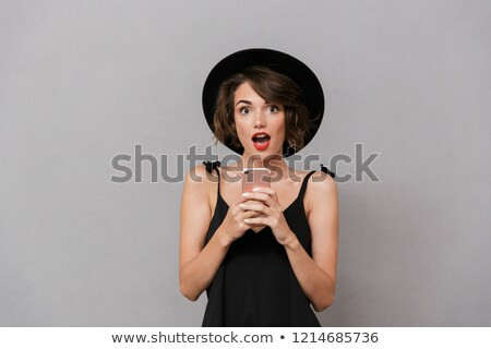 Photo of excited woman 20s wearing black dress and hat smiling a Stock photo © deandrobot