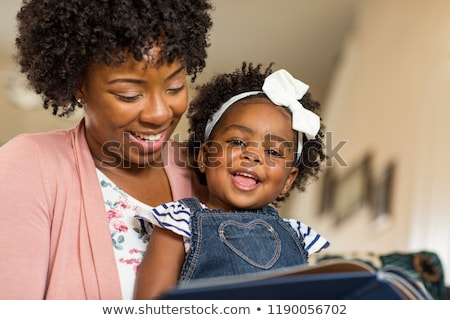 Mother with black child girl on sofa Stock photo © Lopolo
