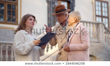 young elegant female agent consulting mature man and woman in office stock photo © pressmaster