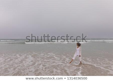 Widok z boku starszy kobieta fali plaży Zdjęcia stock © wavebreak_media