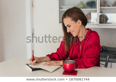 happy woman with notebook drinking cocoa at cafe stock photo © dolgachov